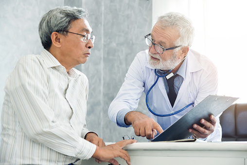 Senior male Doctor is discussing with male patient.